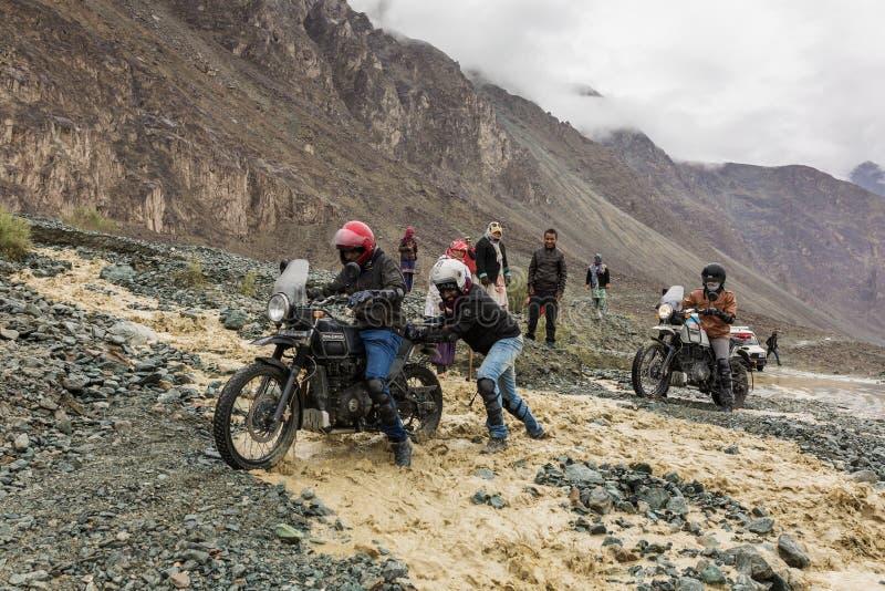 Cyklister som hjälper sig att korsa floden som flödar från smältning av insnöade Himalaya berg, Ladakh region, Indien royaltyfri foto