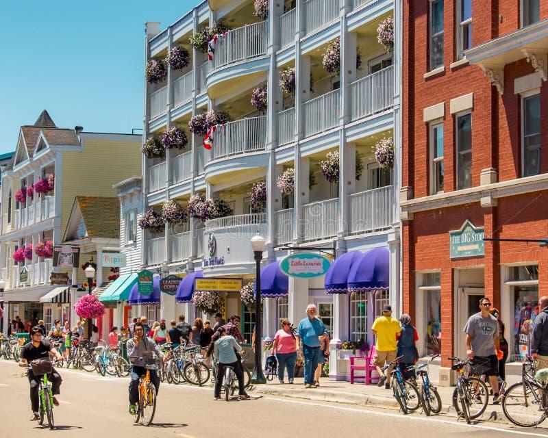 Cyklister som kryssar omkring längs gatorna av den i stadens centrum Mackinac ön under sommaren royaltyfri bild