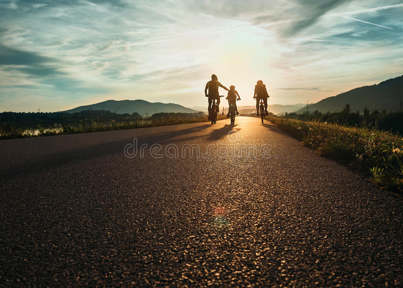 Cyklistfamiljresande på vägen på solnedgången royaltyfri fotografi
