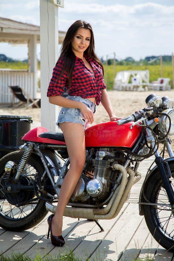 Cyklistflicka på den Retro motorcykeln royaltyfri foto