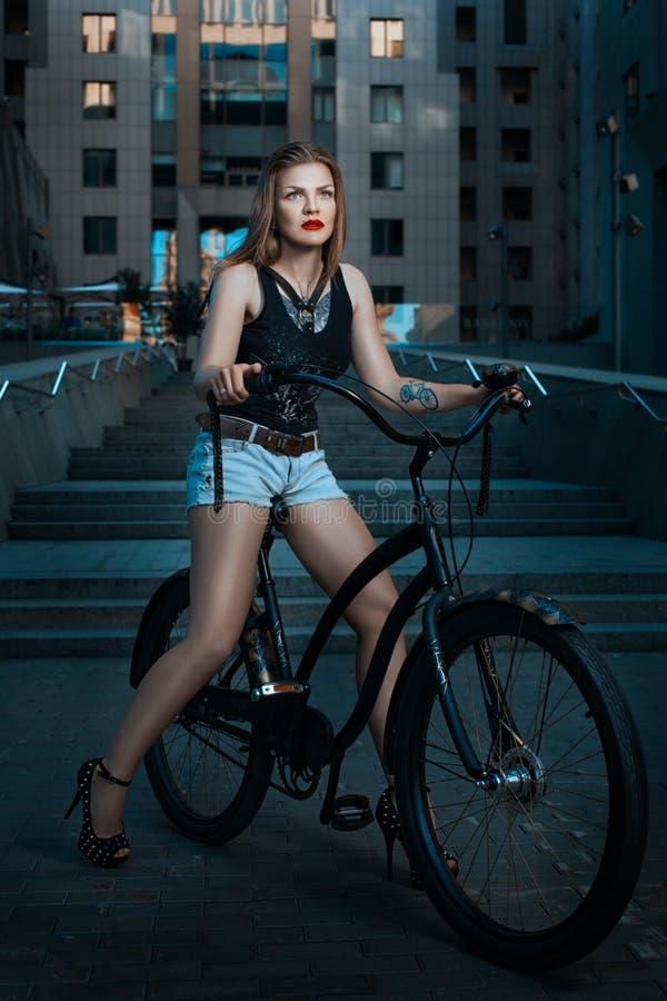 Cyklistflicka på en cykel royaltyfri bild