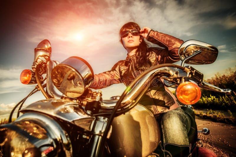 Cyklistflicka på en motorcykel fotografering för bildbyråer