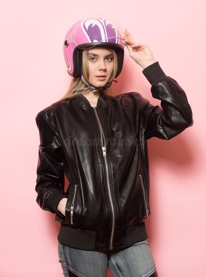 Cyklistflicka som bär den svarta hjälmen för läderomslag och rosa färgmotorcykel royaltyfria foton