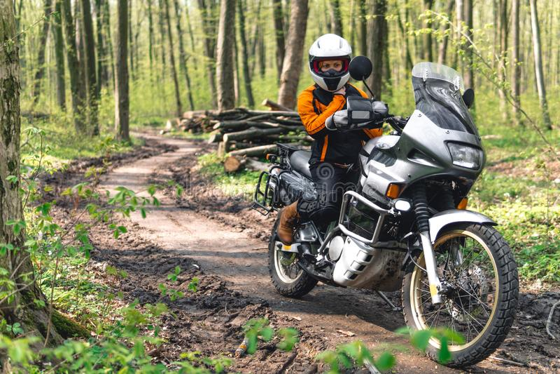 Cyklistflicka som b?r en motorcykeldr?kt, skyddskl?der, utrustning, touristic moped f?r aff?rsf?retag med sidop?sar utomhus- royaltyfria bilder