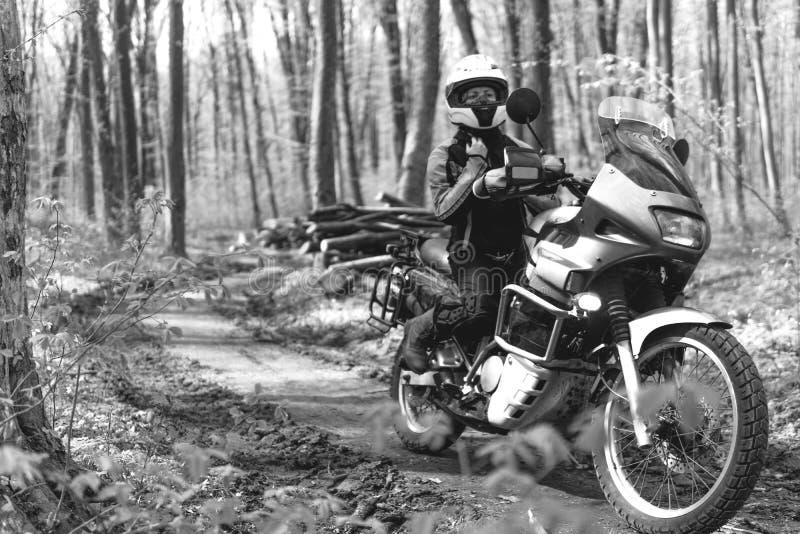 Cyklistflicka som b?r en motorcykeldr?kt, skyddskl?der, utrustning, touristic moped f?r aff?rsf?retag med sidop?sar utomhus- fotografering för bildbyråer