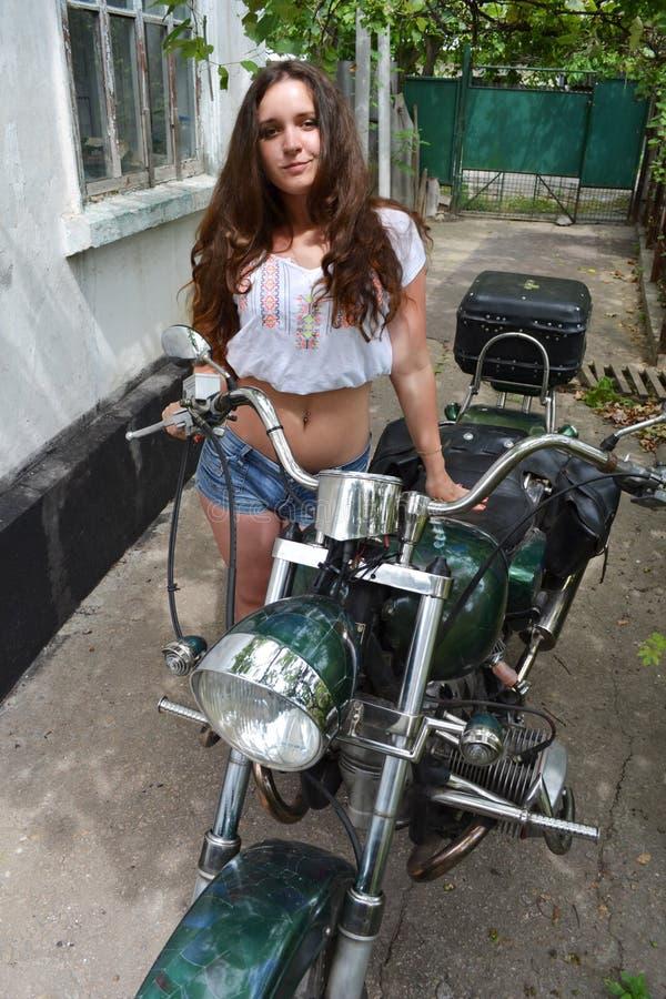 Cyklistflicka som sitter på den beställnings- motorcykeln för tappning Utomhus- livsstil tonad stående royaltyfri bild