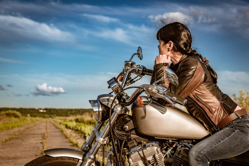 Cyklistflickasammanträde på motorcykeln arkivfoton