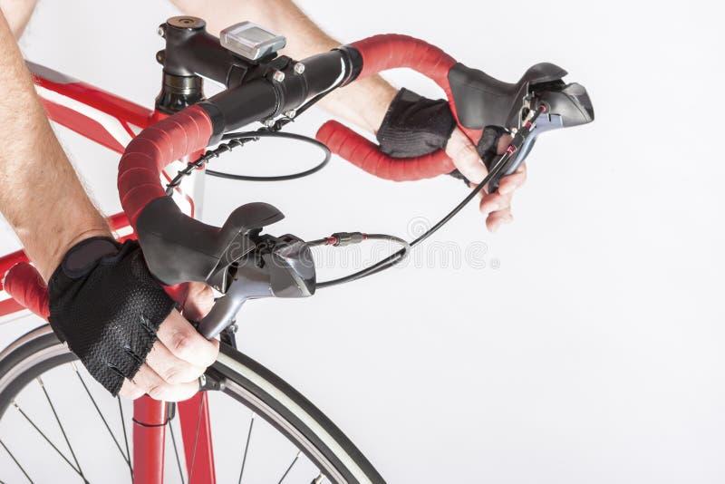 Cyklisthänder i pålagda styren för skyddande handskar Trycka på främre och bakre bromsspakar royaltyfri foto
