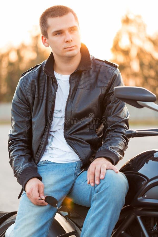 Cyklistman som ut bär ett sammanträde för läderomslag på hans motorcykel arkivbild