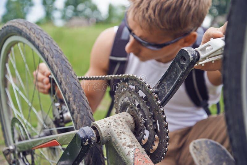 Cyklistmannen kontrollerar kedjan arkivbilder