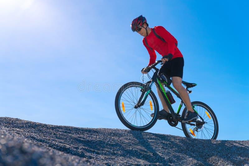 Cyklistridningmountainbike på den steniga slingan på solnedgången arkivbilder