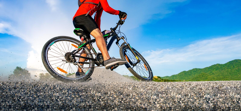 Cyklistridningmountainbike på den steniga slingan på solnedgången, extrem man för mountainbikesportidrottsman nen som rider det f arkivfoto