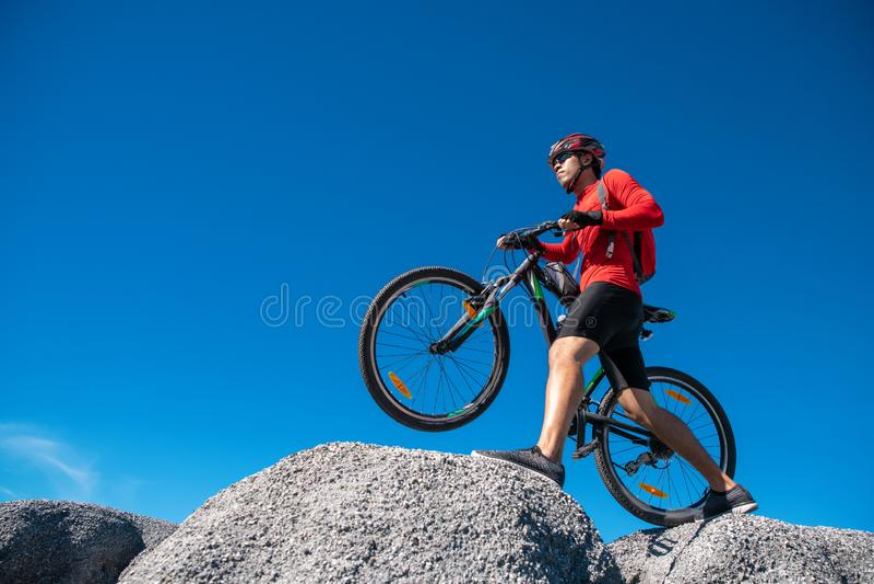 Cyklistridningmountainbike p? den steniga slingan p? solnedg?ngen, extrem man f?r mountainbikesportidrottsman nen som rider det f arkivbilder