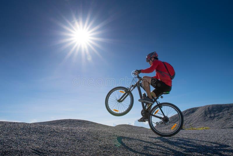 Cyklisty jeździecki rower górski na skalistym śladzie przy zmierzchem, Krańcowy roweru górskiego sporta atlety mężczyzna jedzie o obrazy stock