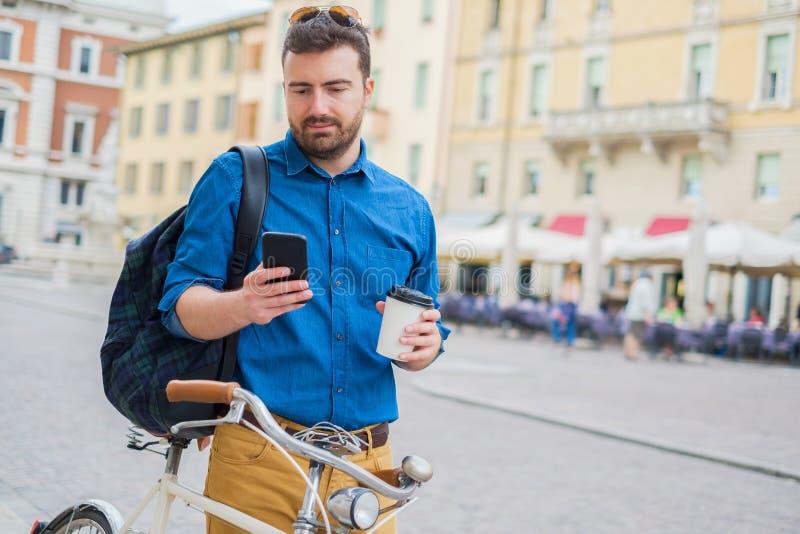 Cyklisty mężczyzna używa telefon komórkowego na zewnątrz czekania na rowerze fotografia stock