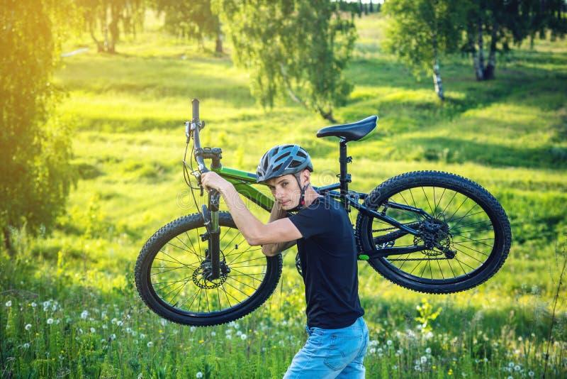 Cyklisty mężczyzna w hełmie niesie jego rower górskiego w wzroscie w tło zieleni naturze Aktywny i zdrowy styl życia zdjęcia royalty free