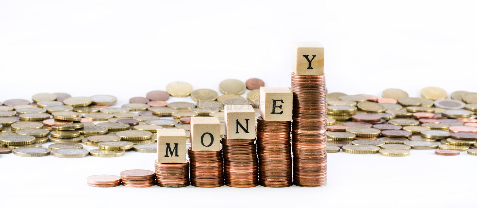 Cylinders of euro coins and the word money formed by wooden little cubes royalty free stock images