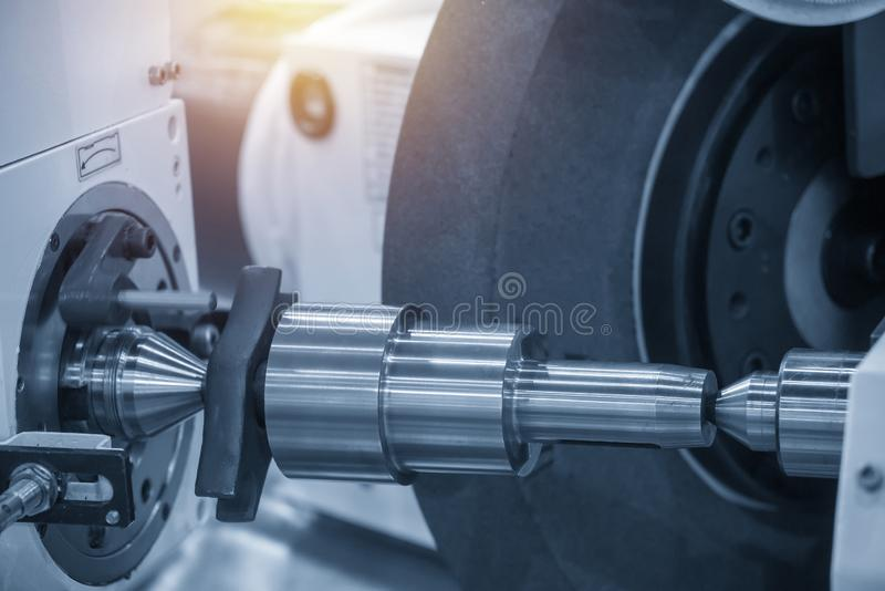 The cylindrical grinding machine with lighting effect. The hi-precision parts manufacturing process by CNC grinding machine stock image