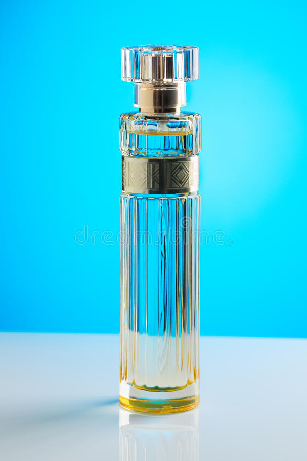 Cylindrical perfume bottle on a blue background. royalty free stock images