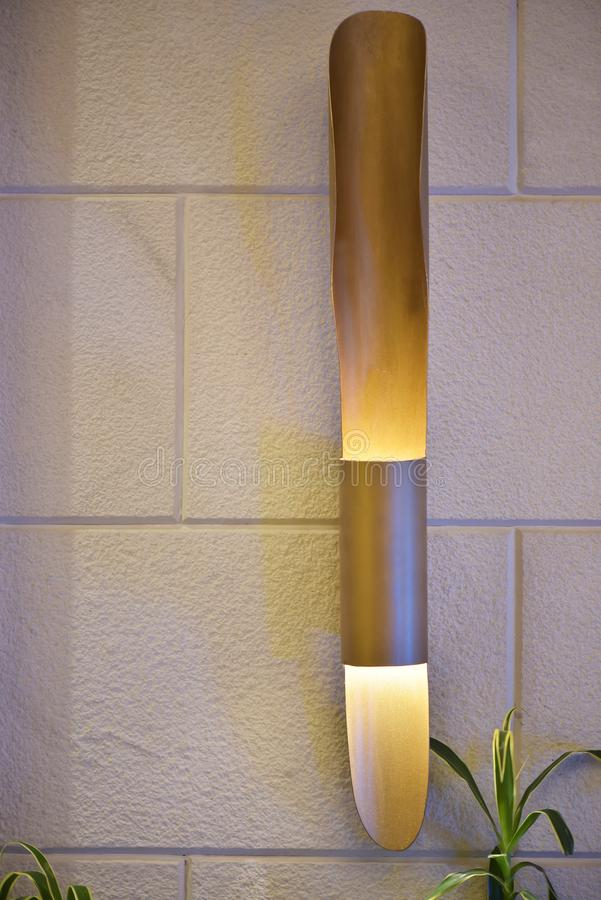 Cylindrical yellow lamp mounted on textured wall royalty free stock image