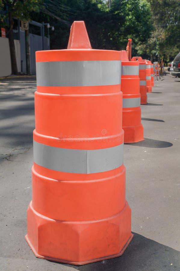 Cylindriska plast- strukturer i orange van vid kontroll trafikerar royaltyfri bild