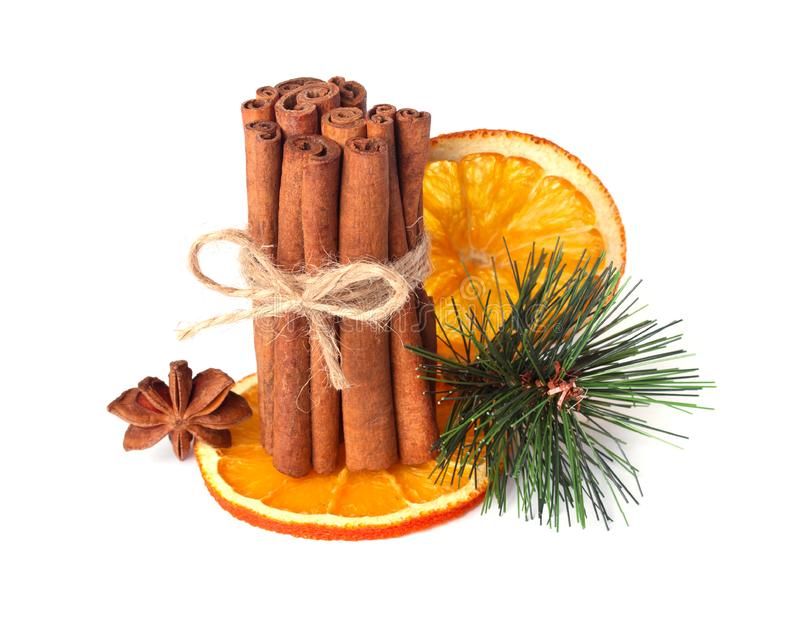 Cynamonowi kije, gwiazdowy anyż, cloves i wysuszona pomarańcze z sztucznymi świerczyn gałązkami odizolowywać na bielu, zdjęcie stock