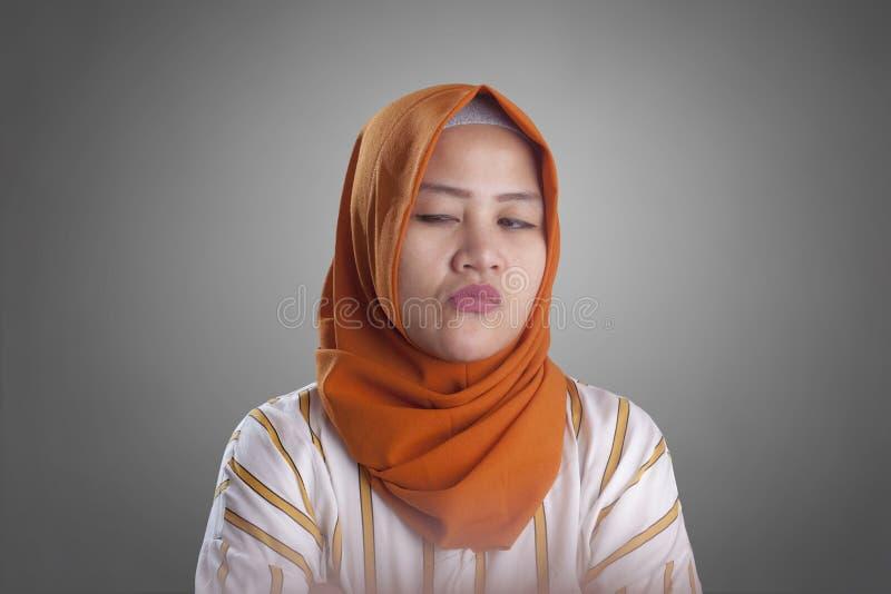 Cynisk muslimsk kvinna som ser till sidan royaltyfri bild