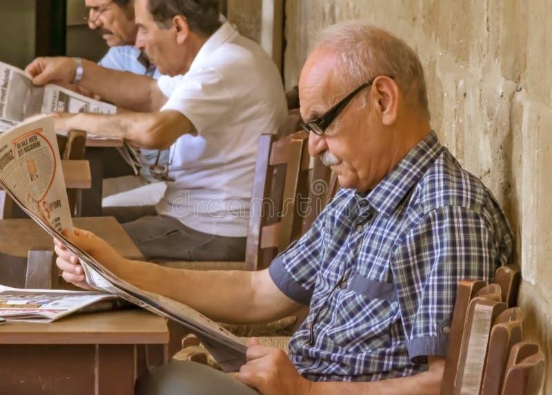 CYPERN NICOSIA - JUNI 10, 2019: Stående av en stilig äldre man 70-80 gamla år läsa en tidning som sitter på tabellen i kafé arkivfoto