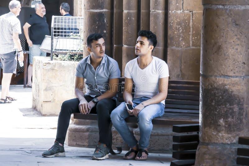 CYPERN NICOSIA - JUNI 10, 2019: Två stiliga grabbar som tillsammans sitter på träbänk bredvid forntida kolonner av det historiskt royaltyfria bilder