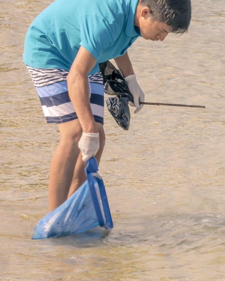 CYPR, KARAVAS, ALSANCAK - CZERWIEC 10, 2019: Młoda chłopiec czyści wybrzeże od gruzów i odpady Azjatycki mężczyzna pracuje używać zdjęcie royalty free