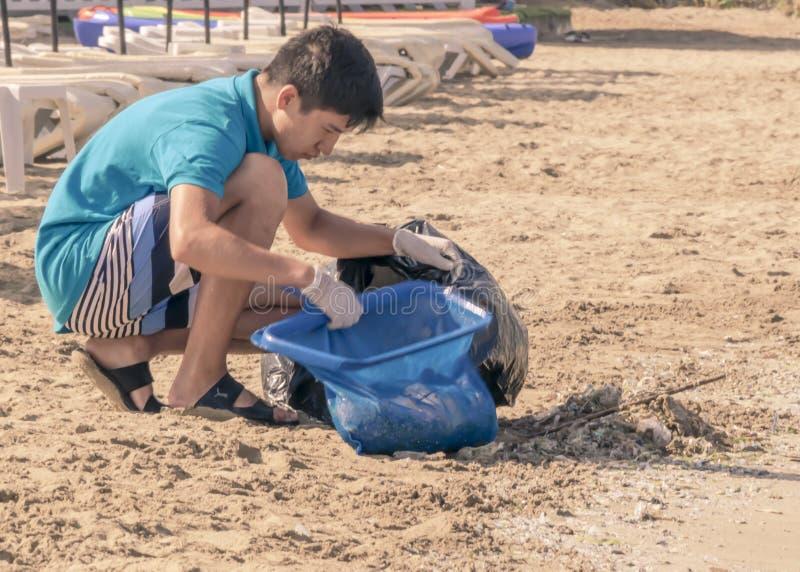 CYPR, KARAVAS, ALSANCAK - CZERWIEC 10, 2019: Młoda chłopiec czyści wybrzeże od gruzów i odpady Mężczyzna pracuje morzem zdjęcia stock