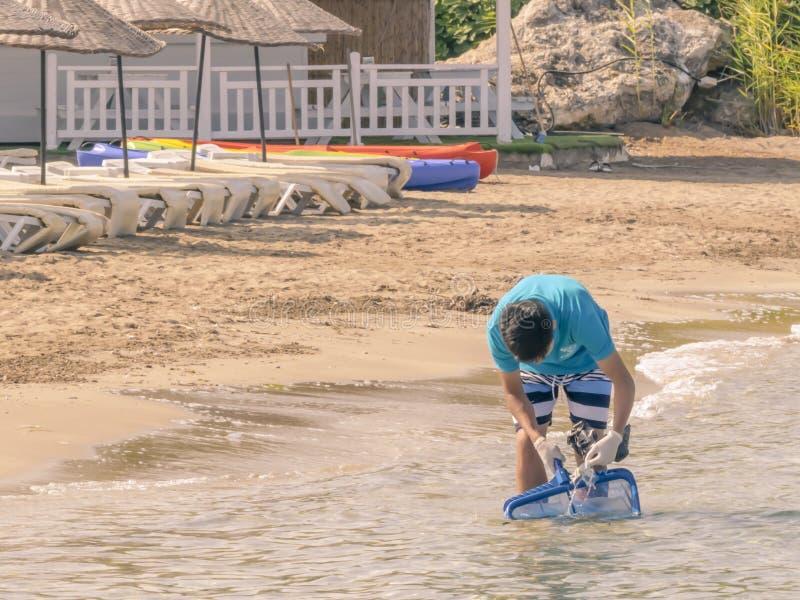 CYPR, KARAVAS, ALSANCAK - CZERWIEC 10, 2019: Młodej azjatykciej chłopiec lata czyści plaża od śmieci Męski działanie używać narzę fotografia royalty free