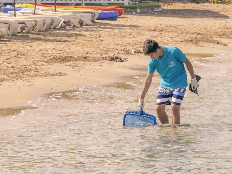 CYPR, KARAVAS, ALSANCAK - CZERWIEC 10, 2019: Młodej azjatykciej chłopiec lata czyści plaża od śmieci Osoba pracuje w wodzie obrazy royalty free