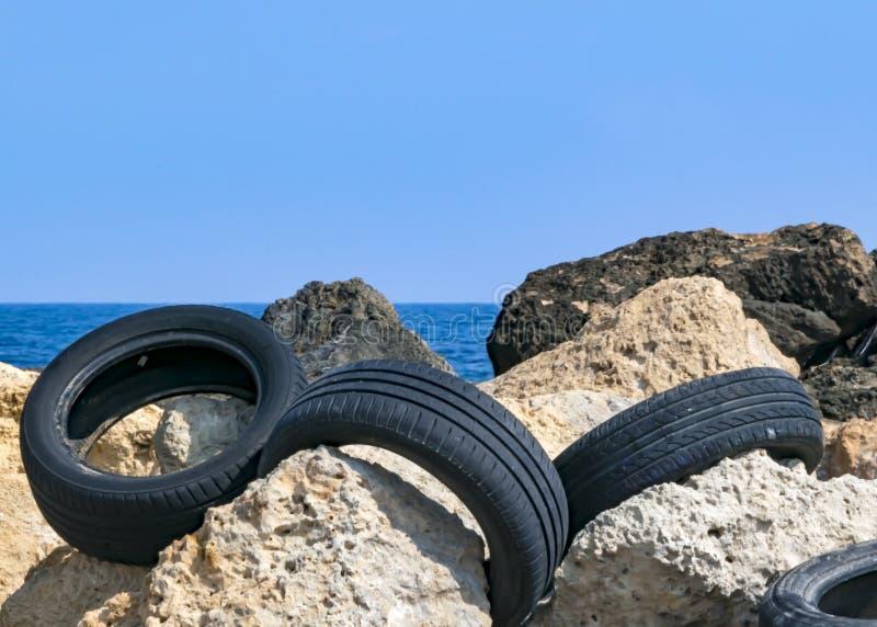CYPR, KARAVAS, ALSANCAK - CZERWIEC 10, 2019: Samochodowe gumowe opony na skałach na nadmorski miejscowy wyrzucać na brzeg ?rodowi zdjęcia stock