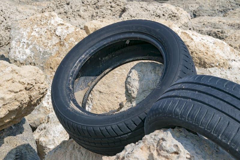 CYPR, KARAVAS, ALSANCAK - CZERWIEC 10, 2019: W górę samochodowych gumowych opon na skałach na brzeg miejscowy plaża fotografia stock