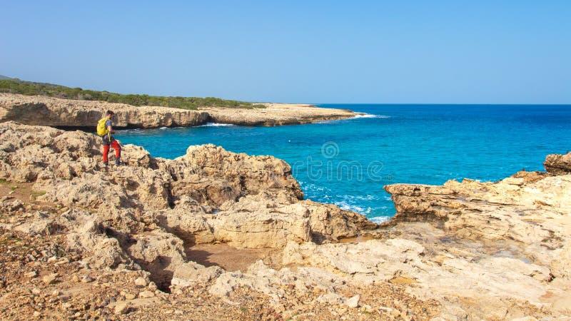 Cypr krajobraz skalisty denny brzeg na słonecznym dniu Cypr seascape z turkus wodą w zatoce Mężczyzn spojrzenia przy morzem macha zdjęcia royalty free
