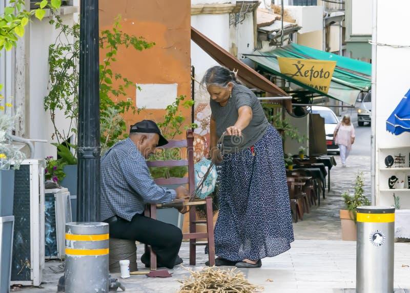 CYPR NIKOZJA, CZERWIEC, - 10, 2019: Starsza Grecka para rzemieślnicy mąż i żona robi łozinowych krzesła na miasto ulicie rodzina fotografia stock