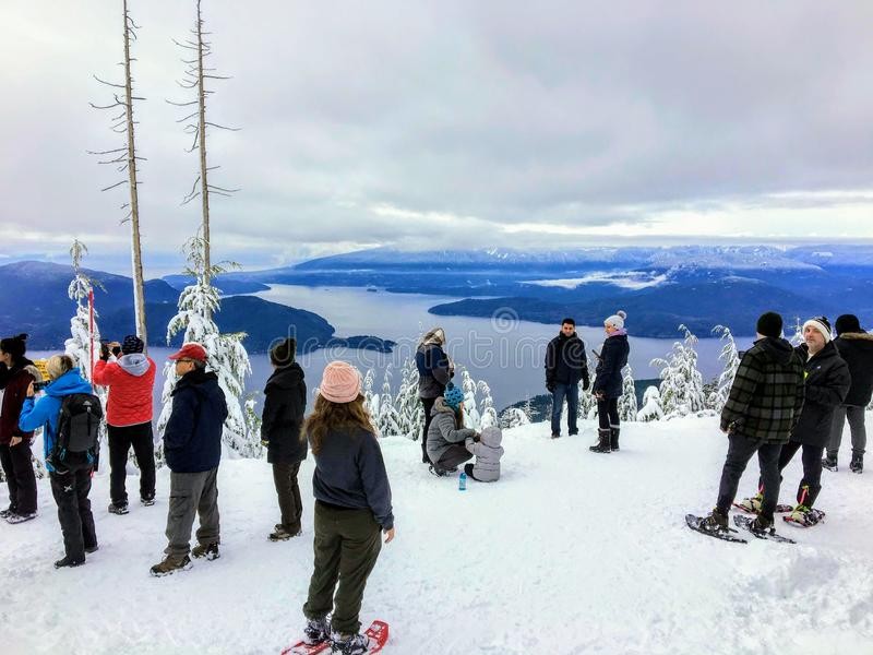 A group of snowshoers admiring the beautiful ocean views of Howe Sound from the Bowen Island Lookout on Cypress Mountain stock photo