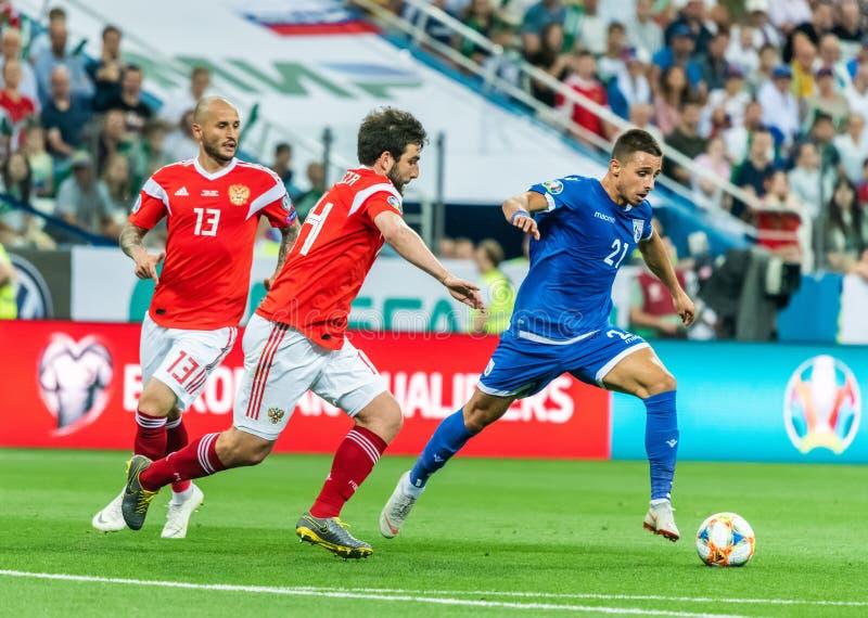 Cypriotisch nationaal team van midfielder Anthony Georgiou tegen Russische spelers Georgi Dzhikiya en Fedor Kudryashov stock fotografie