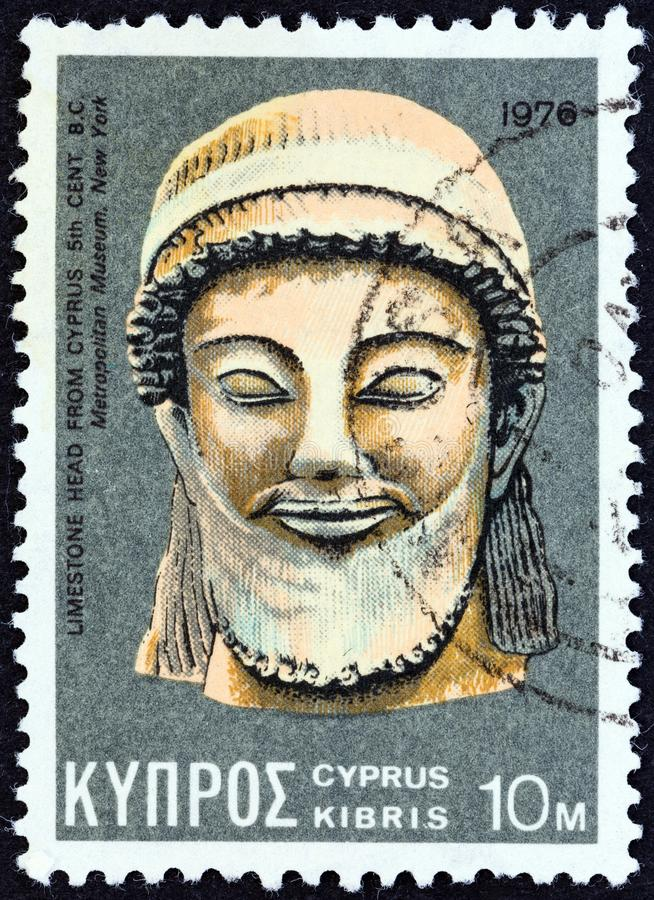 CYPRUS - CIRCA 1976: A stamp printed in Cyprus shows a limestone head from 5th century BC found in Cyprus, circa 1976. CYPRUS - CIRCA 1976: A stamp printed in stock photos