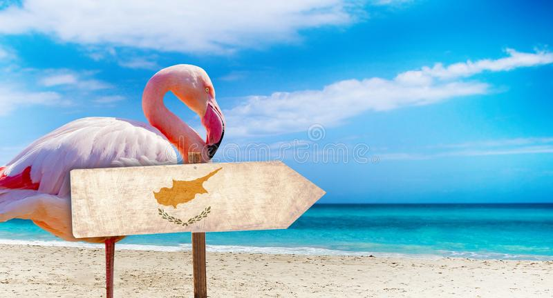 Cyprus flag on wooden table sign on beach background with pink flamingo. There is beach and clear water of sea and blue sky in the. Background. It is tropical stock photography