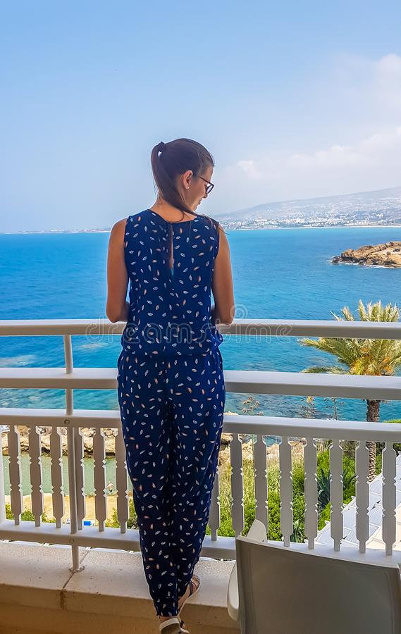 Cyprus - Girl standing on the balcony with a sea view. A young woman standing at the balcony with a view on the sea. She is wearing a spotted jumpsuit. Girl stock images