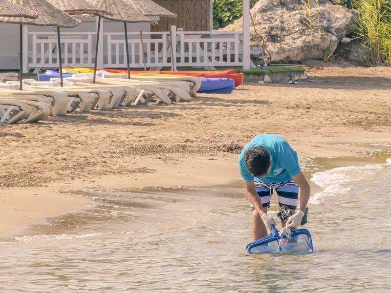 CYPRUS, KARAVAS, ALSANCAK - JUNE 10, 2019: Young asian boy cleaning summer beach from garbage. Male working using tools royalty free stock photography