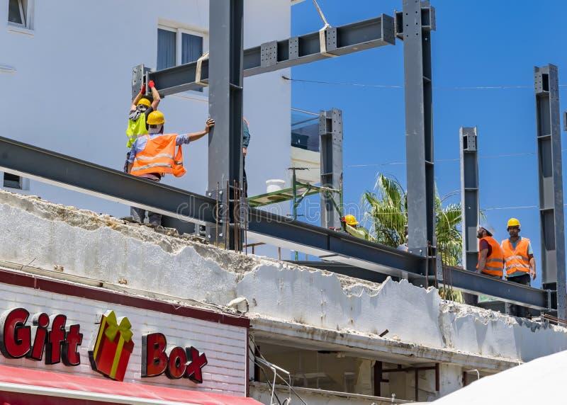CYPRUS, Kyrenia - JUNI 10, 2019: De bouwers bouwen een nieuw gebouw op het dak De arbeiders kleedden zich in oranje vesten en gee stock foto's