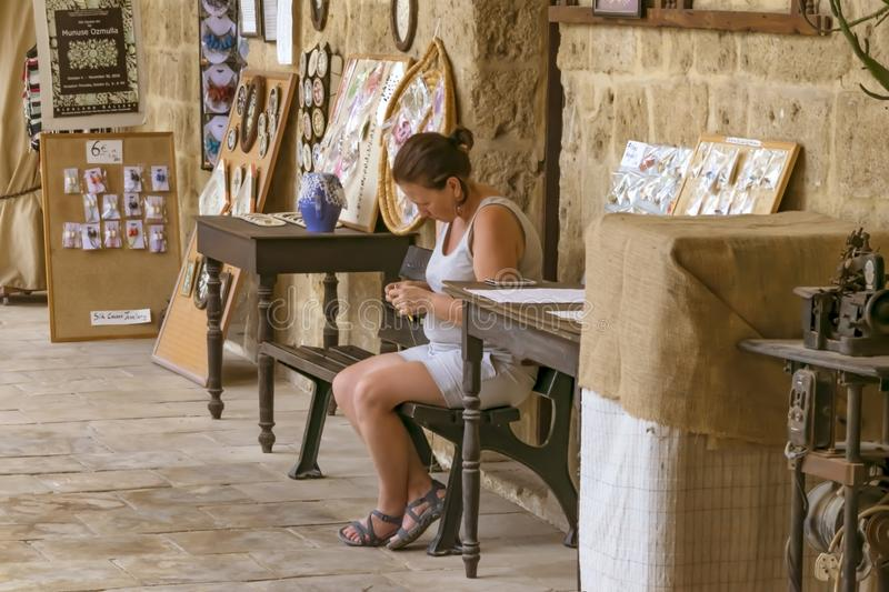 CYPRUS, NICOSIA - JUNE 10, 2019: Portrait of a young female crochet knitter sitting and and working in a local art gallery stock photo