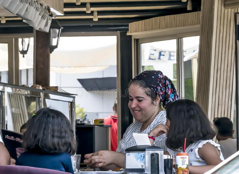 CYPRUS, NICOSIA - JUNE 10, 2019: Young smiling mother in traditional clothes enjoy a meal with two little daughters in open summer royalty free stock photography