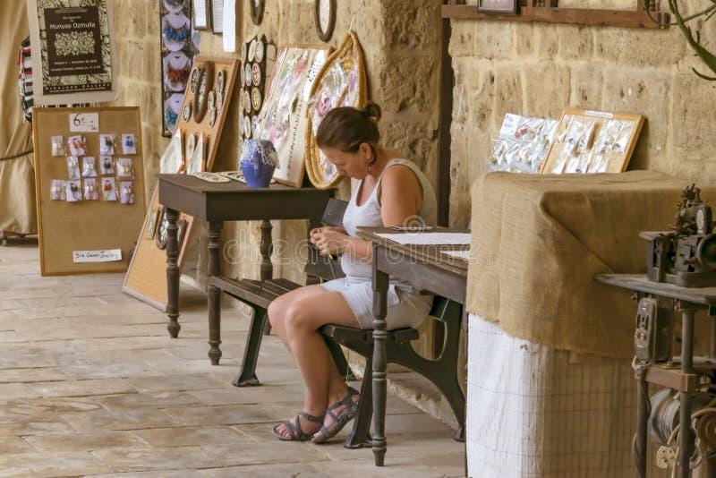 CYPRUS, NICOSIA - JUNI 10, 2019: Het portret van een jong wijfje haakt breisterzitting en en werkend in een lokale kunstgalerie stock foto