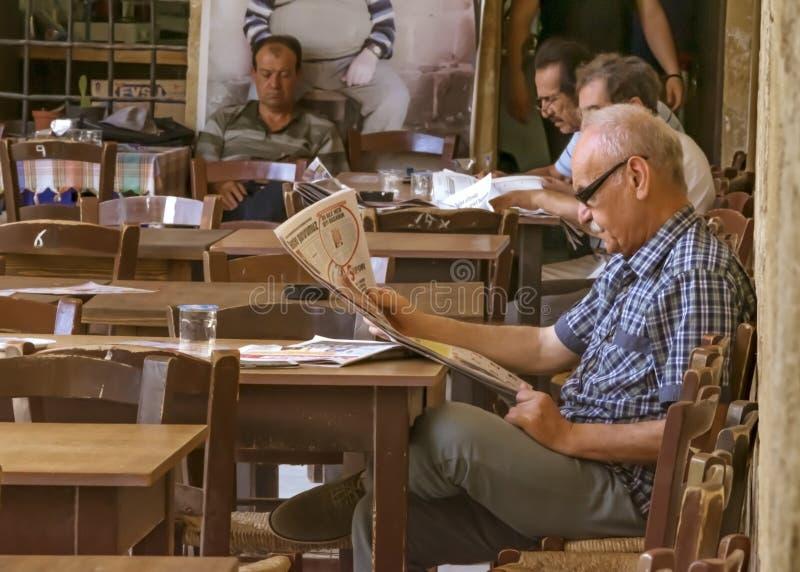 CYPRUS, NICOSIA - JUNI 10, 2019: Knap bejaarde die een krant in een kunstkoffie lezen stock foto