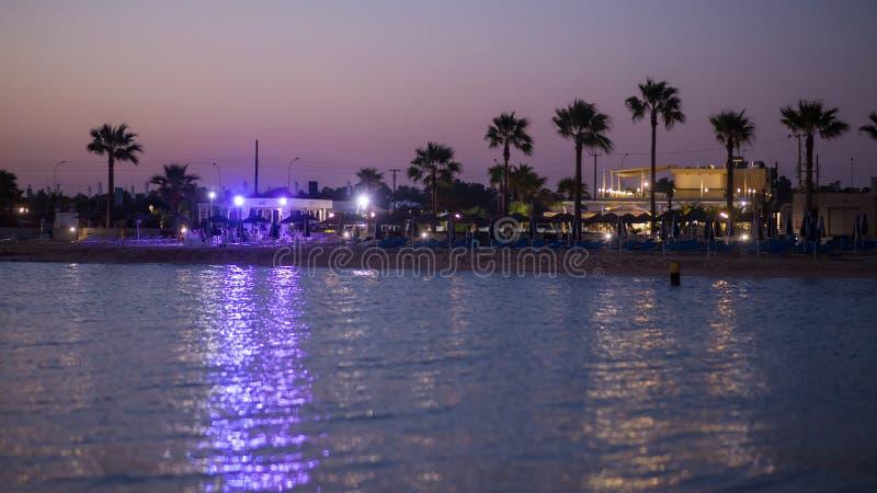 cyprus restaurants en palmen op het strand het gelijk maken vlak na zonsondergang royalty-vrije stock foto's