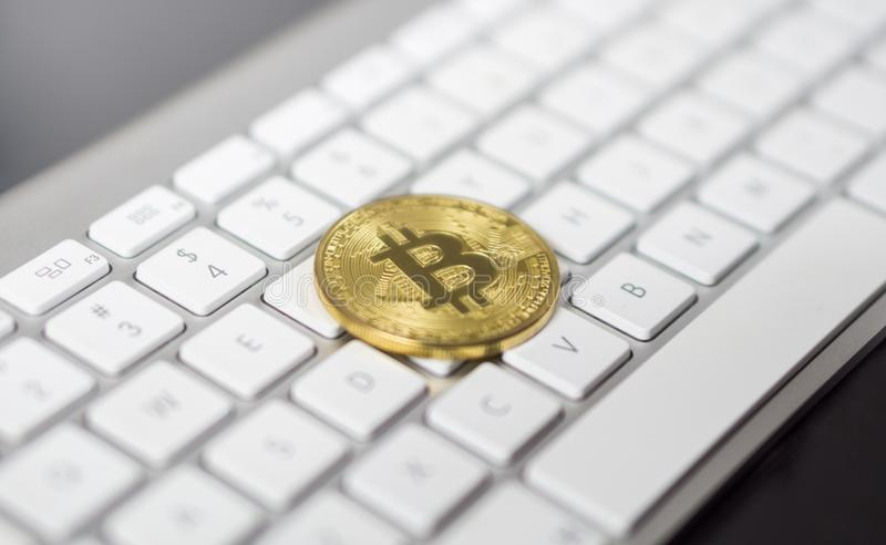 Cyptocurrency golden bitcoin laying down on white keyboard in the background. symbol of electronic virtual money. royalty free stock photo